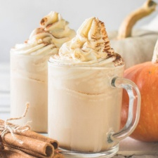 Two glasses of iced pumpkin spice latte with whipped cream, sprinkled with pumpkin spice. You can see cinnamon and pumpkins in the background.